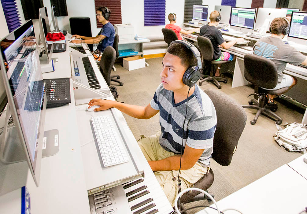 male student sitting in front of computer with headphones on