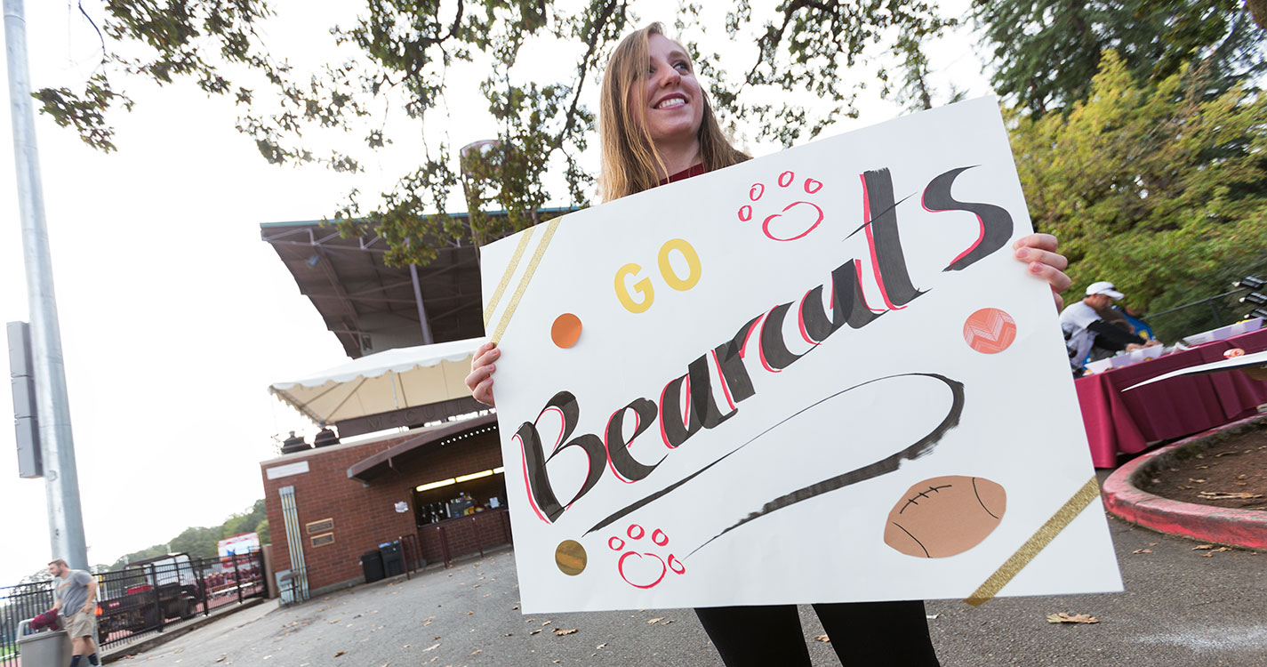 """A student holding a """"Go Bearcats"""" sign at Family Weekend 2017"""