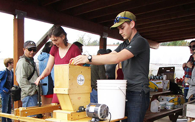 Students use a cider press