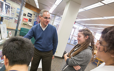 Professor Ricardo De Mambro Santos speaks to three students about an exhibit in Hatfield library