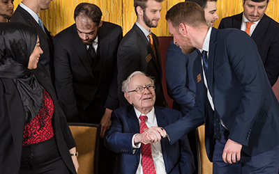 Student from Atkinson Graduate School of Management greets Warren Buffett. Photo by Block 59 Photography