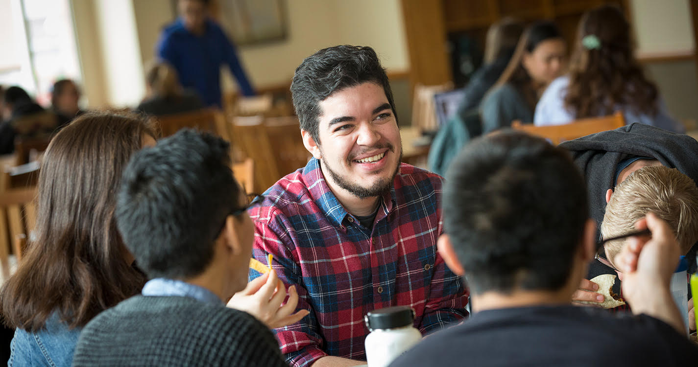 Jose Fausto sitting with friends in Goudy Commons