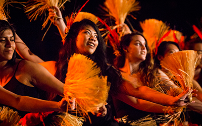 Willamette students dance with fans in the luau