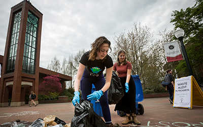 A student wearing rubber gloves sorts trash on a tarp in Jackson Plaza.