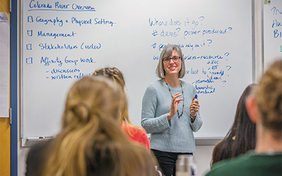 Professor Karen Arabas stands before a classroom with a whiteboard with Overview Colorado River written on it.