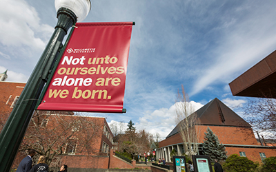 "light post with banner saying ""Willamette University Not unto ourselves alone are we born."" with Roger's Music Hall in background"