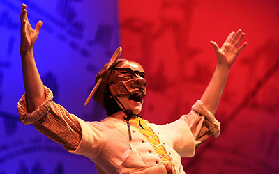 Character wearing wooden mask with hands outstretched in a Y before a blue and red backdrop