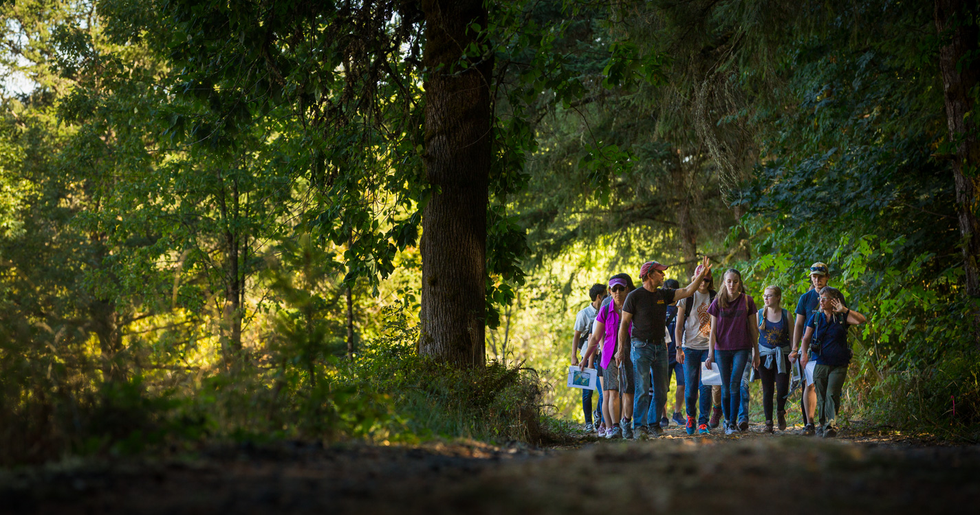 Professor Joe Bowersox leads a group of students through the woods at Willamette's Zena campus.