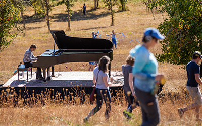 Hunter Noack plays a grand piano in the middle of a field at Willamette's Zena campus