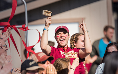 A fan in Bearcat attire smiles at cheers among the crowd at a soccer game