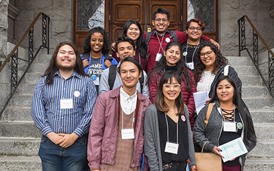 Eleven Willamette students stand on the steps of a building at the Pacific Northwest Students of Color Conference at Gonzaga University