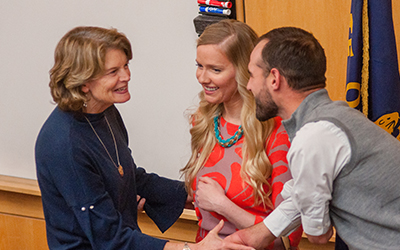 Sen. Lisa Murkowski greets two students with a handshake.