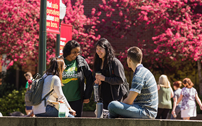 four students converse in Jackson Plaza in spring
