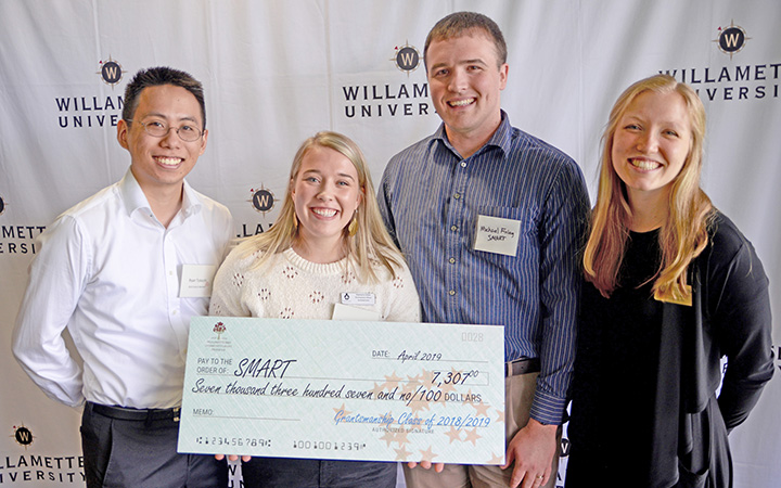 students present check to grant recipient