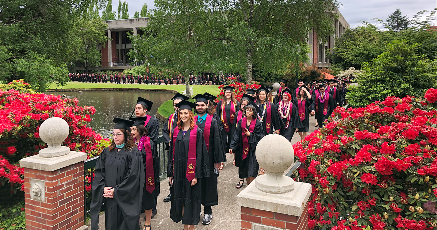 CLA students in commencement procession line the sidewalks around the Mill Stream