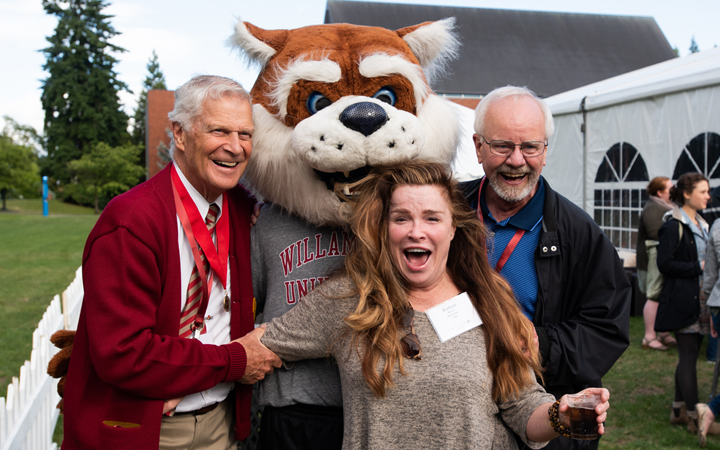 three alumni pose with Blitz the Bearcat