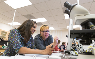 student and professor crouch over a computer screen next to a microscope