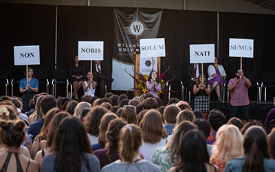 From the crowd's perspective on the Quad, five student hold signs of Willamette's motto in Latin: non nobis solum nati sumus