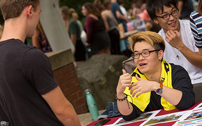 A smiling student seated at a table outside helps a standing student sign up for a club