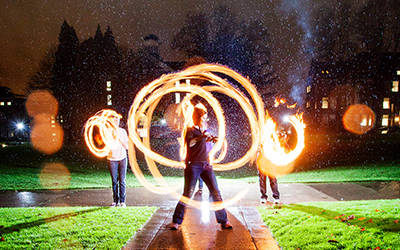three students twirl flaming poi in a time-lapse photo so the fire forms circles around them