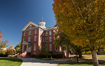 Waller Hall on a sunny autumn day with orange-yellow tree in foreground