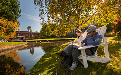 two students sit under a tree in Adirondack chairs along the Mill Stream while reading