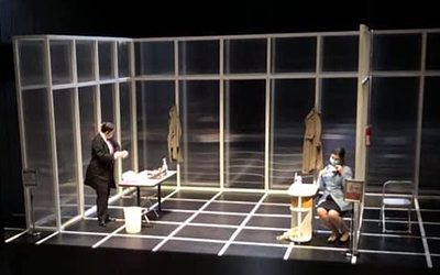 two actors wear masks on a black stage set marked with a white grid