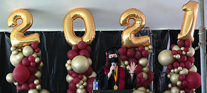 Cameron Taggesell speaks before balloons that spell 2021